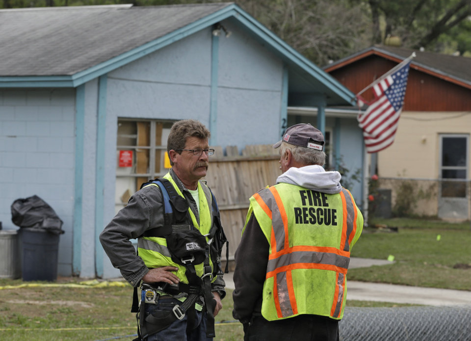 Engineers talk in front of a home, where a sinkhole opened up underneath a bedroom late Thursday evening and swallowed a man, in Seffner, Fla. on Saturday, March 2, 2013. Jeffrey Bush, 37, was in his bedroom Thursday night when the earth opened and took him and everything else in his room. Five other people were in the house but managed to escape unharmed. Bush\'s brother jumped into the hole to try to help, but he had to be rescued himself by a sheriff\'s deputy. (AP Photo/Chris O\'Meara)