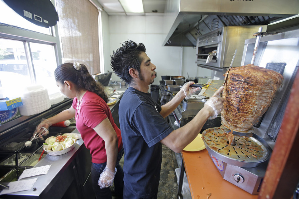 Photo - This Aug. 1, 2014 photo shows a cook shaving meat seasoned with chipotle and guajillo peppers at  Chunga's in Salt Lake City. In Chunga's, a spit turns layers of smoky, marinated pork known as Pastor.  The hunt for a taste of Mexico City brings diners here near a highway overpass in a neighborhood known for tire shops and tacos. (AP Photo/Rick Bowmer)