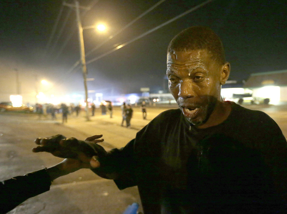 Photo - A man tries to recover after being treated for tear gas during a protest Monday, Aug. 18, 2014, for Michael Brown, who was killed by a police officer Aug. 9 in Ferguson, Mo. Brown's shooting has sparked more than a week of protests, riots and looting in the St. Louis suburb. (AP Photo/Charlie Riedel)