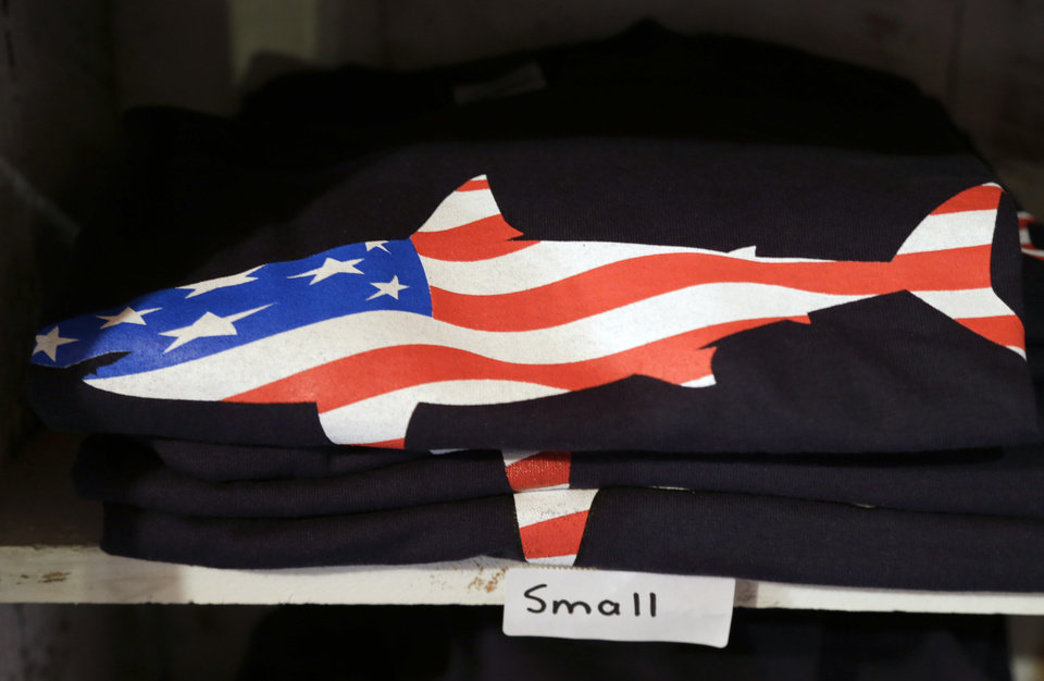 Photo - In this July 2, 2014 photo, a T-shirt with a likeness of a shark incorporating an American flag rests on a shelf in a souvenir shop in Chatham, Mass. With growing sightings of great white sharks off Cape Cod, local entrepreneurs are feeding the frenzy with their shark-themed memorabilia and apparel. (AP Photo/Steven Senne)