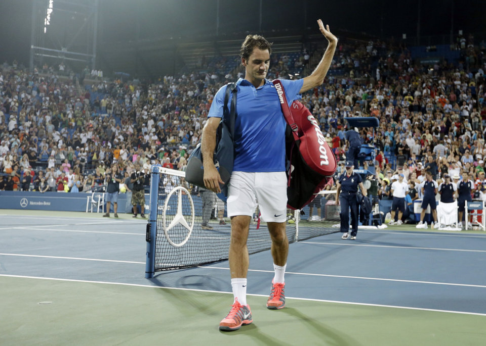 Photo - Roger Federer, of Switzerland, walks off the court after losing in straight sets to Tommy Robredo, of Spain, during the fourth round of the 2013 U.S. Open tennis tournament, Monday, Sept. 2, 2013, in New York. (AP Photo/Darron Cummings)