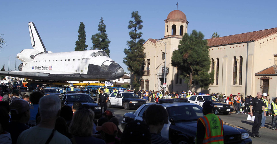 Photo -   Spectators watch the space shuttle Endeavour slowly move down Martin Luther King Blvd. in Los Angeles Sunday, Oct. 14, 2012. In thousands of Earth orbits, the space shuttle Endeavour traveled 123 million miles. But the last few miles of its final journey are proving hard to get through. Endeavour's 12-mile crawl across Los Angeles to the California Science Museum hit repeated delays Saturday, leaving expectant crowds along city streets and at the destination slowly dwindling. Officials estimated the shuttle, originally expected to finish the trip early Saturday evening, would not arrive until later Sunday. (AP Photo/Alex Gallardo)