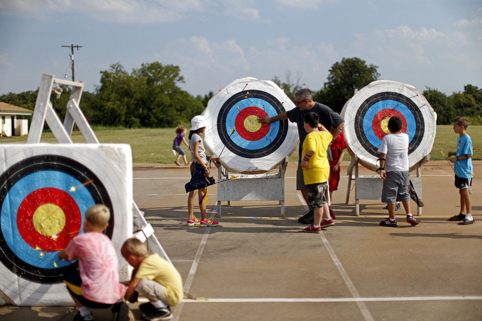 Photo - Archers gather around targets to collect their arrows during a Junior Olympic Archery Development Club shoot put on by the Trosper Archery Club on Saturday, August 24, 2013, at Trosper Park in Oklahoma City.  Over 60 participants, from beginners to intermediates, took part in the shoot which takes place every Saturday. For $5 each person is supplied with equipment and instruction starting at 9am for beginners and 10am for intermediate shooters. Photo by Bryan Terry, The Oklahoman