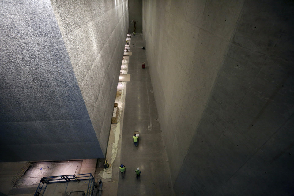 Photo - Contractors work at the National September 11 Memorial and Museum, Friday, Sept. 6, 2013 in New York. Construction is racing ahead inside the museum as the 12th anniversary of the Sept. 11, 2001 attacks draws near. Several more large artifacts have been installed in the cavernous space below the World Trade Center memorial plaza. (AP Photo/Mary Altaffer)