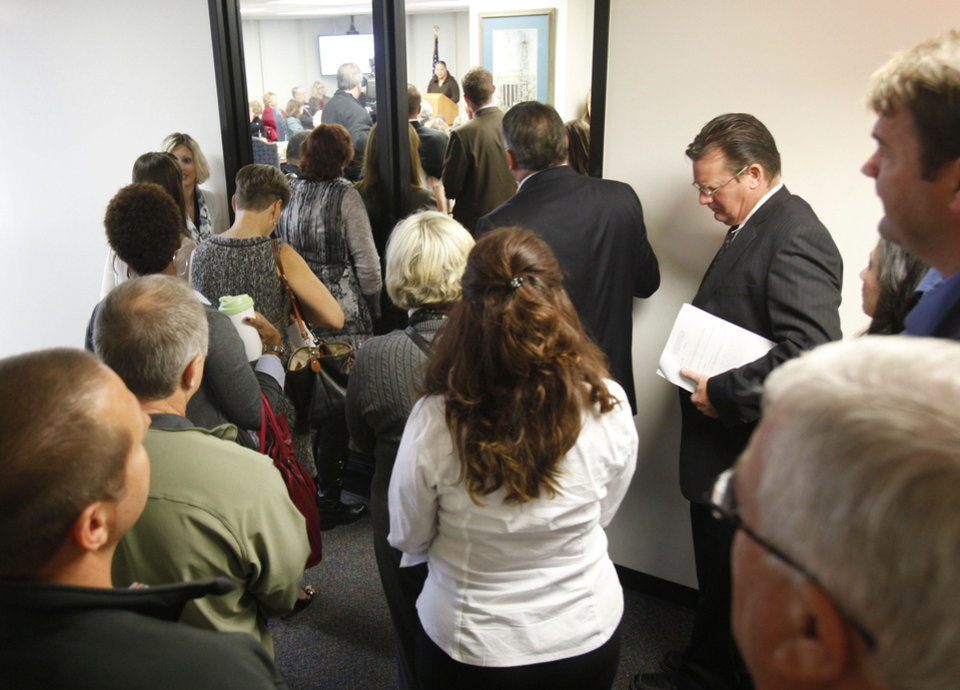 Photo - A standing-room-only crowd overflows into a hallway during a state Board of Education meeting Thursday in Oklahoma City.  Photo by Paul Hellstern, The Oklahoman