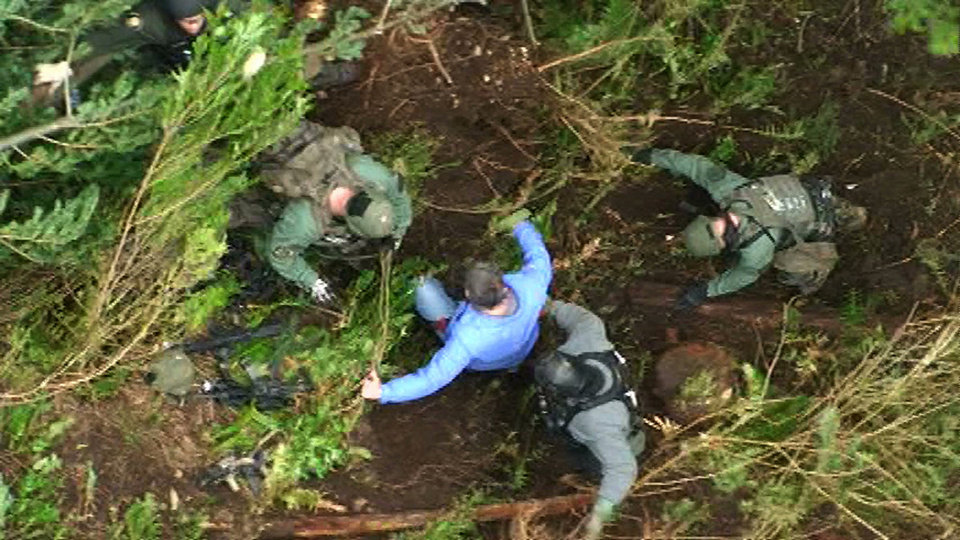 Photo -   In this still frame taken from video provided by the King Co. Sheriff's Dept., a detective, center, is helped to the ground by other law-enforcement officers after he was lowered from a helicopter to an area near a deep-woods bunker, Saturday, April 28, 2012, in North Bend, Wash. Police, who had surrounded the bunker since Friday, found a dead body inside on Saturday. Authorities earlier said they believed that Peter A. Keller, who is suspected of killing his wife and daughter last week, was hiding out in the bunker. (AP Photo/King Co. Sheriff's Dept.)