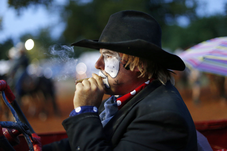 Second-generation rodeo barrelman Shane Parli smokes a cigar that he uses in his show as he waits to perform during the annual LibertyFest Rodeo. Parli's two children help him perform some of the same acts he helped his father with when he was a child. PHOTO BY BRYAN TERRY, THE OKLAHOMAN. <strong>Bryan Terry - THE OKLAHOMAN</strong>
