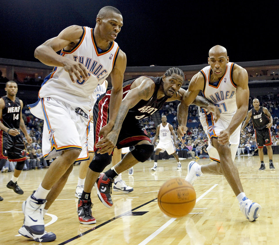 Photo - Oklahoma City's Russell Westbrook, left, and Michael Ruffin fight for the ball beside Miami's Udonis Haslem during an NBA preseason game between the Oklahoma City Thunder and the Miami Heat at the BOK Center in Tulsa, Okla., Wednesday, October 14, 2009. Photo by Bryan Terry, The Oklahoman