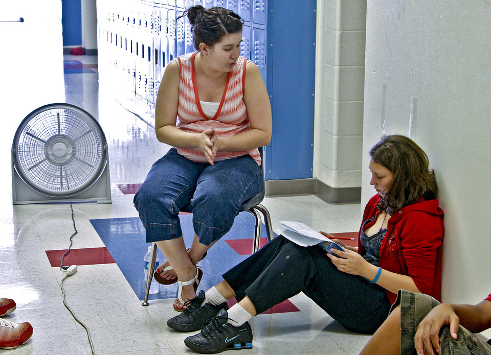 John Marshall High School math teacher Cassi Yarbrough works with student in front of a fan as she teaches her class in the hallway to help keep the students cooler while there was no air conditioning at John Marshall High School on Friday, March 30 2012, in Oklahoma City, Oklahoma.  Photo by Chris Landsberger, The Oklahoman