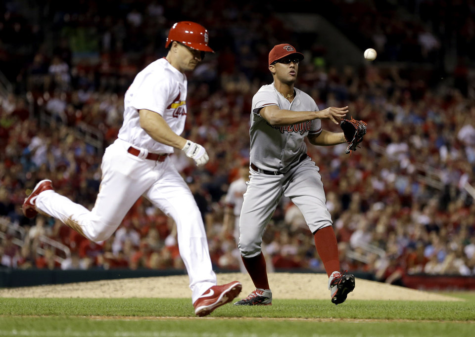 Photo - Arizona Diamondbacks relief pitcher Randall Delgado, right, throws St. Louis Cardinals' Mark Ellis,left, out at first during the eighth inning of a baseball game Thursday, May 22, 2014, in St. Louis. (AP Photo/Jeff Roberson)