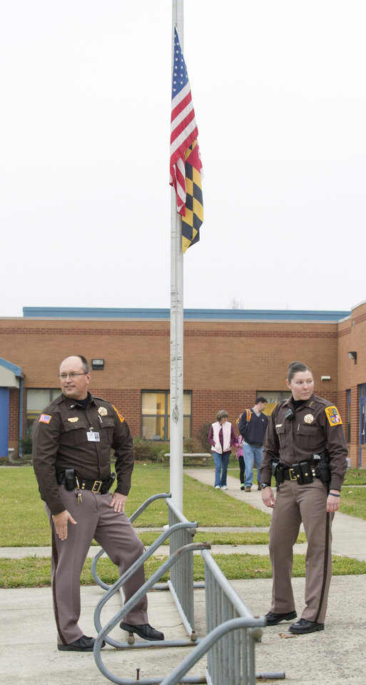 Photo - Frederick County Sheriff's officers stand outside an elementary school Monday, Dec. 17, 2012, in Frederick, Md. Deputies were making an appearance at all county elementary schools in response to the shootings last week in Connecticut. The deputies were at the school at the start and end of the day. (AP Photo/The Frederick News-Post, Bill Green) ORG XMIT: MDFRE101