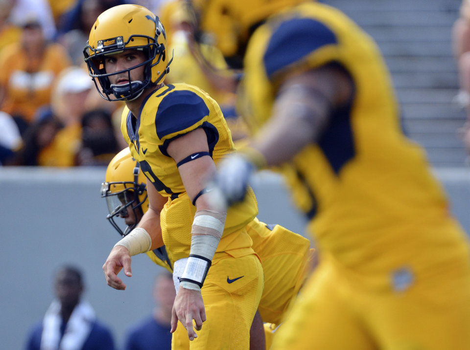 Photo - West Virginia quarterback Clint Trickett (9) signals his reciever during the third quarter of an NCAA college football game against Oklahoma State in Morgantown, W.Va., on Saturday, Sept. 28, 2013. (AP Photo/Tyler Evert) ORG XMIT: WVTE306