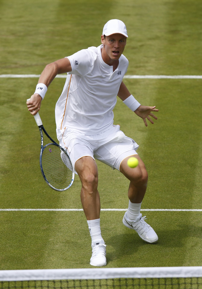 Photo - Tomas Berdych of the Czech Republic plays a return to Victor Hanescu of Romania during their first round match at the All England Lawn Tennis Championships in Wimbledon, London,  Monday, June  23, 2014. (AP Photo/Sang Tan)
