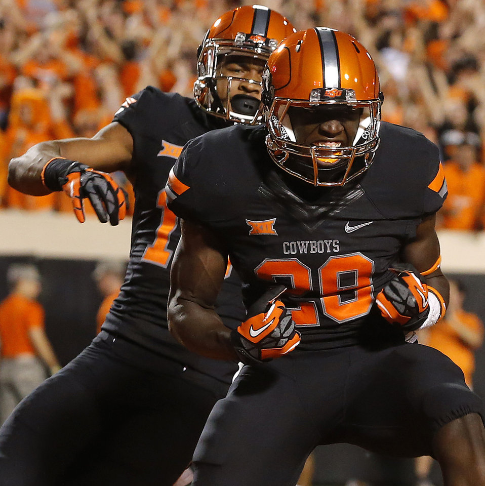 Photo - Oklahoma State's James Washington (28) and Chris Lacy (15) celebrate after Washington's touchdown during a college football game between the Oklahoma State Cowboys (OSU) and the Texas Tech Red Raiders at Boone Pickens Stadium in Stillwater, Okla., Thursday, Sept. 25, 2014. Photo by Bryan Terry, The Oklahoman
