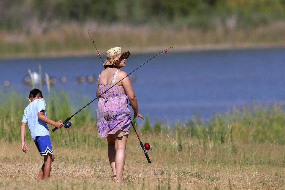Maria Loera and son, Angel Loera, 8, look for a fishing spot on the banks of Crystal Lake. The Oklahoma City Police Athletic League and the Oklahoma City  parks department teamed up to organize a fishing clinic for kids, aged  5-15, Saturday morning, July 21, 2012.  Organizers at the event said 50 children showed up to cast their fishing lines and lures into Crystal Lake on SW 15, west of MacArthur Blvd.  Most children were accompanied by an adult.   Photo by Jim Beckel, The Oklahoman.