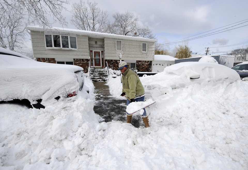 Photo - Susan Kelly digs out two cars parked in front of her home on 17th Street after a snow storm on Saturday, Feb. 9, 2013 in Bayville, N.Y. The downstairs of her home was flooded by Superstorm Sandy. The roof blew off and the ceiling collapsed. A storage container in the driveway still holds many household items. A howling storm across the Northeast left the New York-to-Boston corridor shrouded in 1 to 3 feet of snow Saturday, stranding motorists on highways overnight and piling up drifts so high that some homeowners couldn't get their doors open. More than 650,000 homes and businesses were left without electricity. (AP Photo/Kathy Kmonicek)