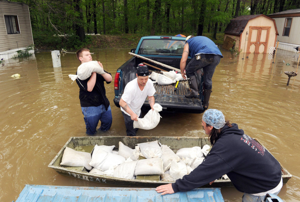 Photo - David Leslie, right, hauls sand bags with friends, Chad Riley, center, Taz Bowman, 18, left, and Tim O'Neal, back, to the levee behind the Pleasant Ridge Mobile Home Park in Evansville, Ind. on Wednesday, April 27, 2011.  Pigeon Creek snakes behind the area and is dangerously close to flowing over the levee. Most of the water in the park is from rain and from water that is coming back up through the storm drains.