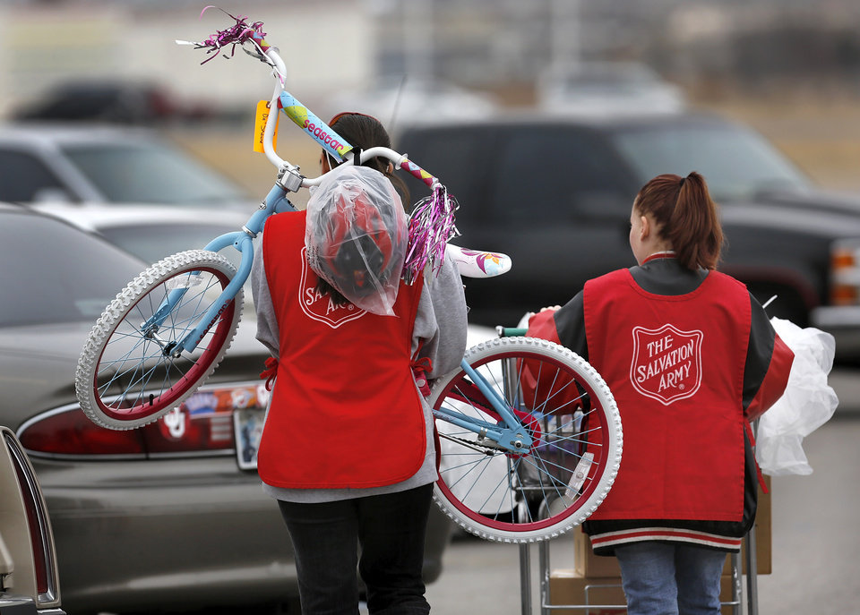 Michelle King of Midwest City carries a bicycle on her shoulders as she and fellow volunteer Alexandria Parks of Del City carry a client's gifts to a car in the parking lot at Crossroads Mall. Today was King and Parks' first time to volunteer at this event.  The Salvation Army and Feed the Children teamed to distribute bicycles and toys for children,  and handed out boxes of food for families at their annual distribution event Wednesday, Dec. 19, 2012. Salvation Army officials said 100 volunteers helped make the event go smoothly. The volunteers loaded bags of toys and bikes into vehicles of clients who had been pre-approved for assistance.  Many of the gifts were provided through the Salvation Army's Angel Tree program   Photo by Jim Beckel, The Oklahoman