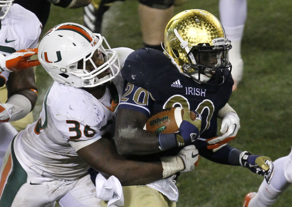 Photo -   Notre Dame running back Cierre Wood (20) carries the ball and is tackled by Miami linebacker Gionni Paul during the second half of an NCAA college football game at Soldier Field, Saturday, Oct. 6, 2012, in Chicago. Notre Dame won 41-3. (AP Photo/Charles Rex Arbogast)