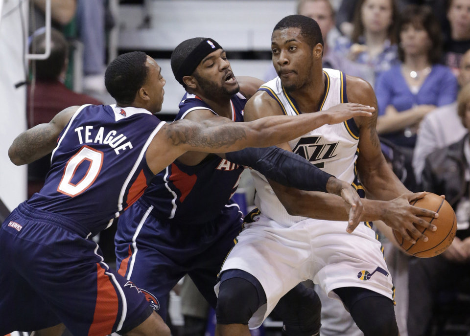 Atlanta Hawks' Jeff Teague (0) and Josh Smith, center, guard Utah Jazz's Derrick Favors during the first quarter of an NBA basketball game Wednesday, Feb. 27, 2013, in Salt Lake City. (AP Photo/Rick Bowmer)