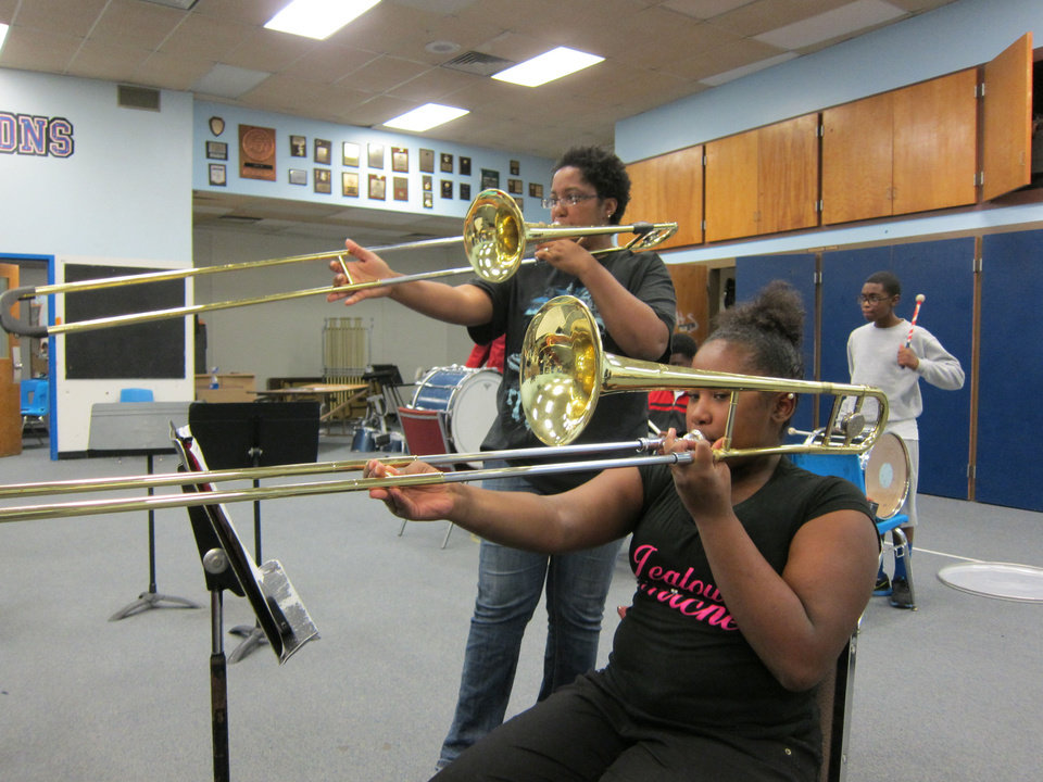 Class of 1997 graduate Rahgna Lewis, 33, of Junction City, Kan., plays trombone alongside her cousin, seventh-grader Kendra Cosby, 12, during Saturday's Millwood High School marching band practice at the school, 6724 N Martin Luther King Avenue. <strong>Carla Hinton - The Oklahoman</strong>