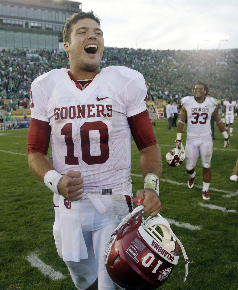 Photo - Oklahoma's Blake Bell (10) celebrates after defeating Notre Dame 35-21 in an NCAA college football game on Saturday, Sept. 28, 2013, in South Bend, Ind. (AP Photo/Darron Cummings)  ORG XMIT: INDC113
