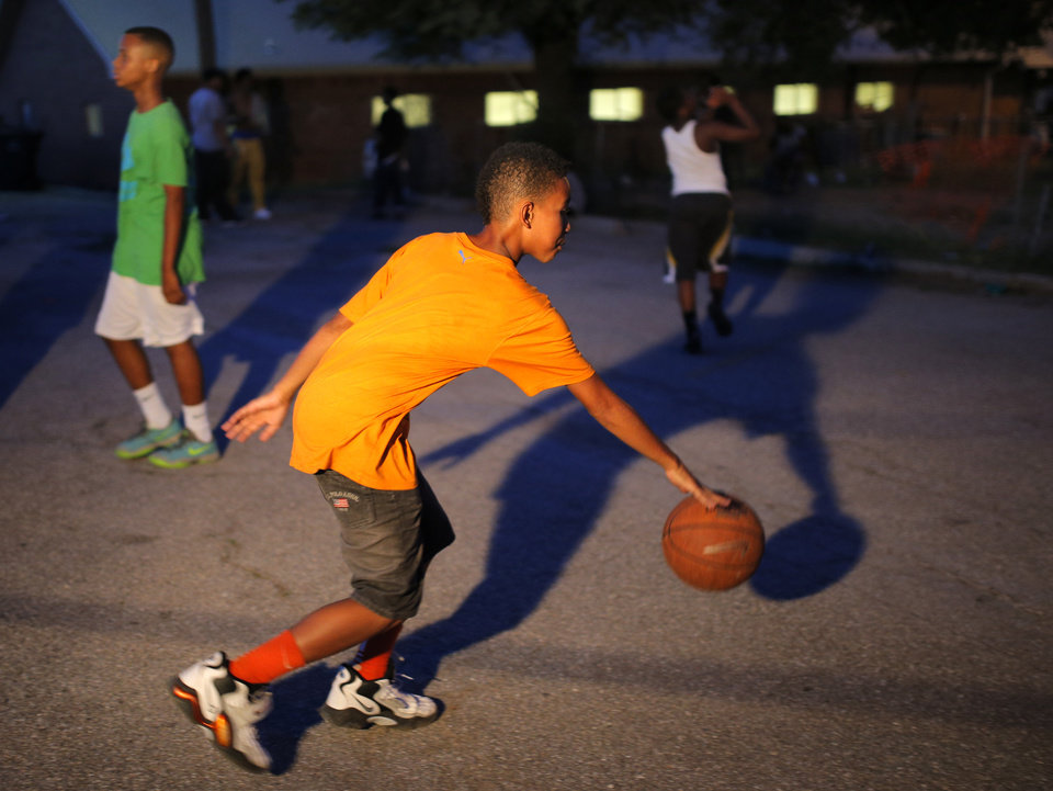 Photo - A youth drives to the basket during midnight basketball at Christ Temple Community Church in Oklahoma City, Friday, July 25, 2014. Photo by Sarah Phipps, The Oklahoman