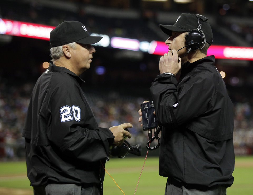 Photo - MLB umpires Pat Hoberg (20) and Chris Guccione review a play challenged by San Francisco Giants manager Bruce Bochy (15) in the fourth inning during a baseball game against the Arizona Diamondbacks, Tuesday, April 1, 2014, in Phoenix. (AP Photo/Rick Scuteri)