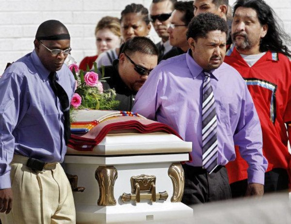 Photo - Pallbearers carry the casket of Rosalin Reynolds, 8, from her funeral service Thursday at the Watonga High School gym to a hearse. Rosalin was found fatally stabbed in Watonga last week.  JIM BECKEL - The Oklahoman