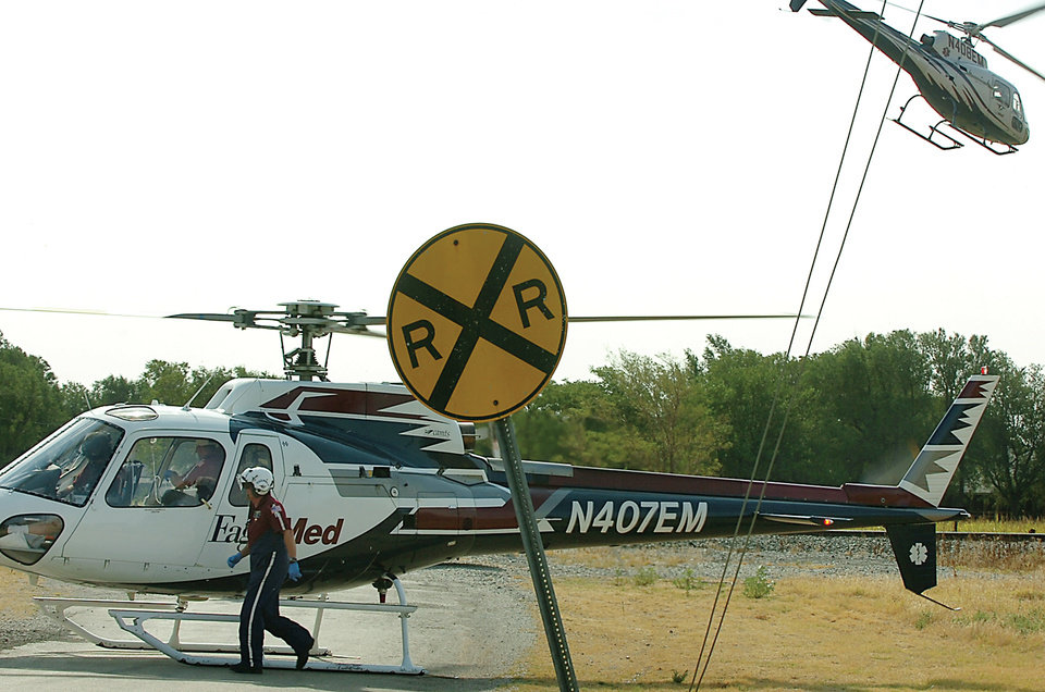 Photo - A pilot of an Eagle-Med helicopter prepares to take off as another ambulance begins its flight to OU Medical Center in Oklahoma City after two 17-year-olds were injured and extricated from a grain auger at Zaloudek Grain Company Thursday, August 4, 2011, in Kremlin, Okla.  Tyler Zander and Bryce Gannon were transported in critical condition. Photo by Cass Rains, Enid News and Eagle