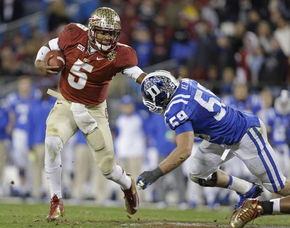 Photo - FILE - In this Dec. 7, 2013, file photo, Florida State quarterback Jameis Winston (5) scrambles as Duke's Kelby Brown (59) defends in the first half of the Atlantic Coast Conference Championship NCAA football game in Charlotte, N.C. Winston has the opportunity to accomplish what only one other player has achieved _ win consecutive Heisman trophies. (AP Photo/Bob Leverone, File)