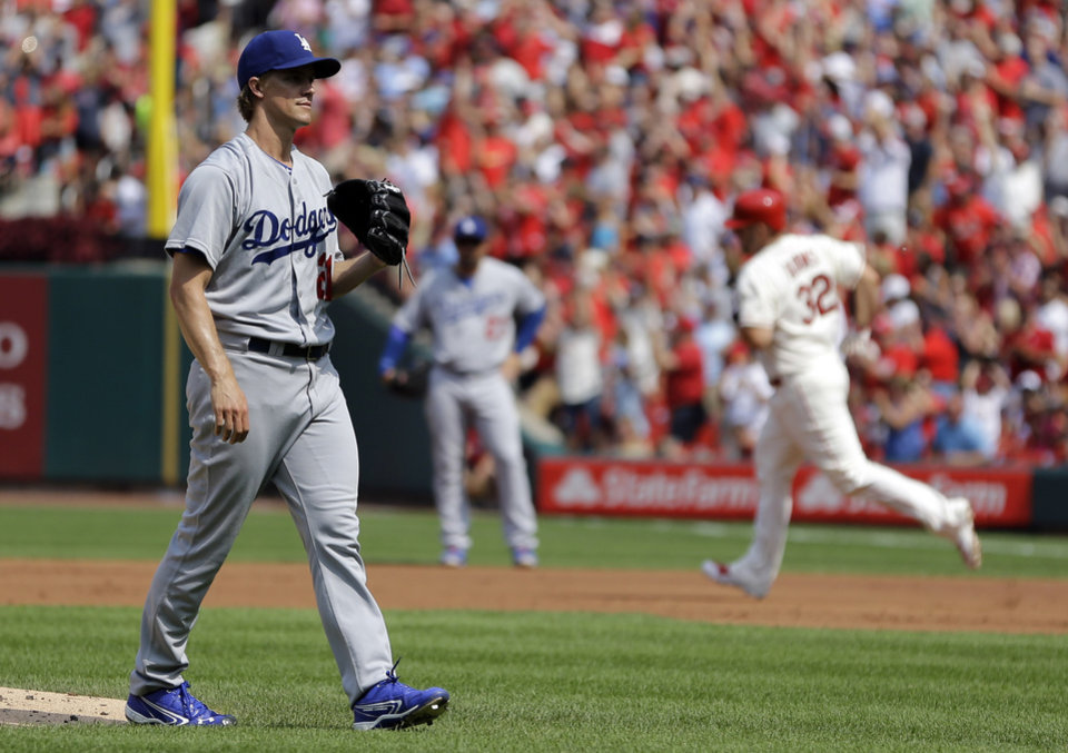 Photo - St. Louis Cardinals' Matt Adams, right, rounds the bases after hitting a two-run home run off Los Angeles Dodgers starting pitcher Zack Greinke, left, during the first inning of a baseball game Saturday, July 19, 2014, in St. Louis. (AP Photo/Jeff Roberson)