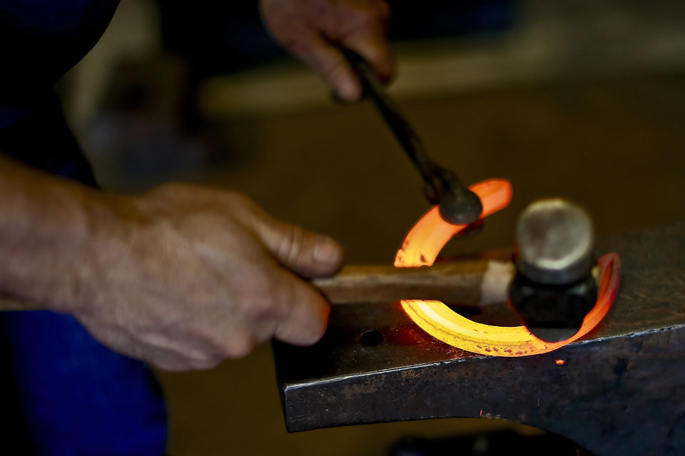 Photo -      World champion horseshoer Mark Milster works at the anvil at his shop in Goldsby. Milster was recently inducted into the International Horseshoeing Hall of Fame.    CHRIS LANDSBERGER -  CHRIS LANDSBERGER