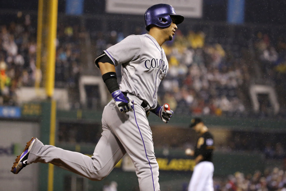 Photo - Colorado Rockies' Carlos Gonzalez, left rounds third after hitting a two run home run off Pittsburgh Pirates starting pitcher Charlie Morton, right rear, during the seventh inning of a baseball game in Pittsburgh Saturday, July 19, 2014. (AP Photo/Gene J. Puskar)