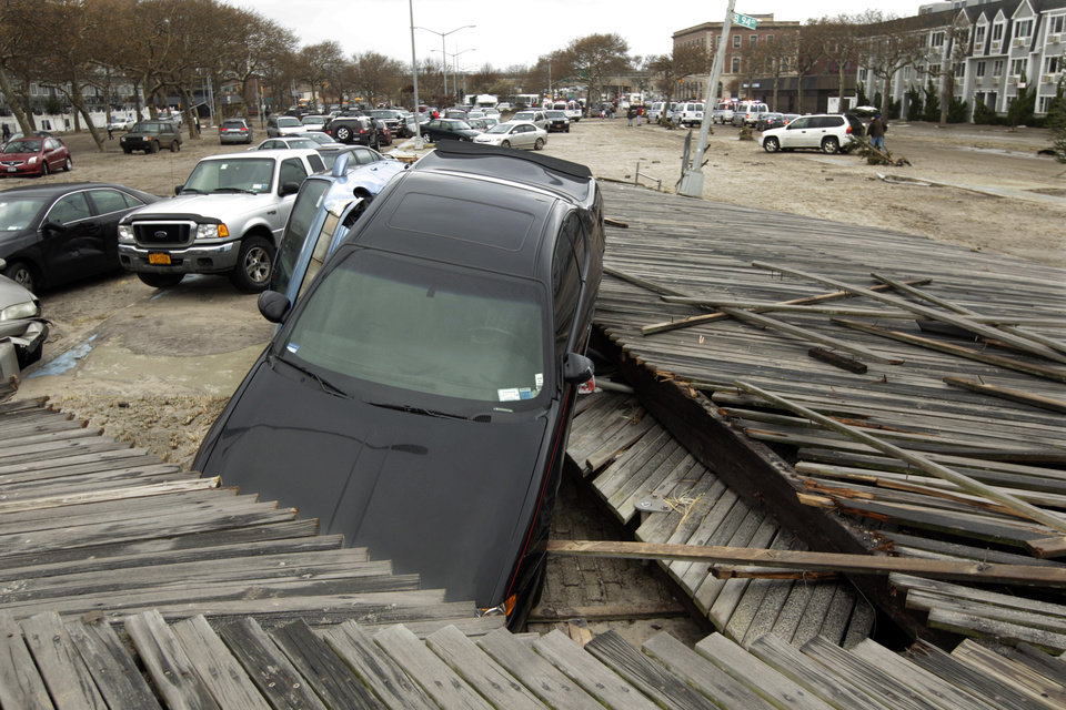 Pedestrians walk past the boardwalk and cars displaced by superstorm Sandy, near Rockaway Beach in the New York City borough of Queens, Tuesday, Oct. 30, 2012, in New York. Sandy, the storm that made landfall Monday, caused multiple fatalities, halted mass transit and cut power to more than 6 million homes and businesses. (AP Photo/Frank Franklin II) ORG XMIT: NYFF146