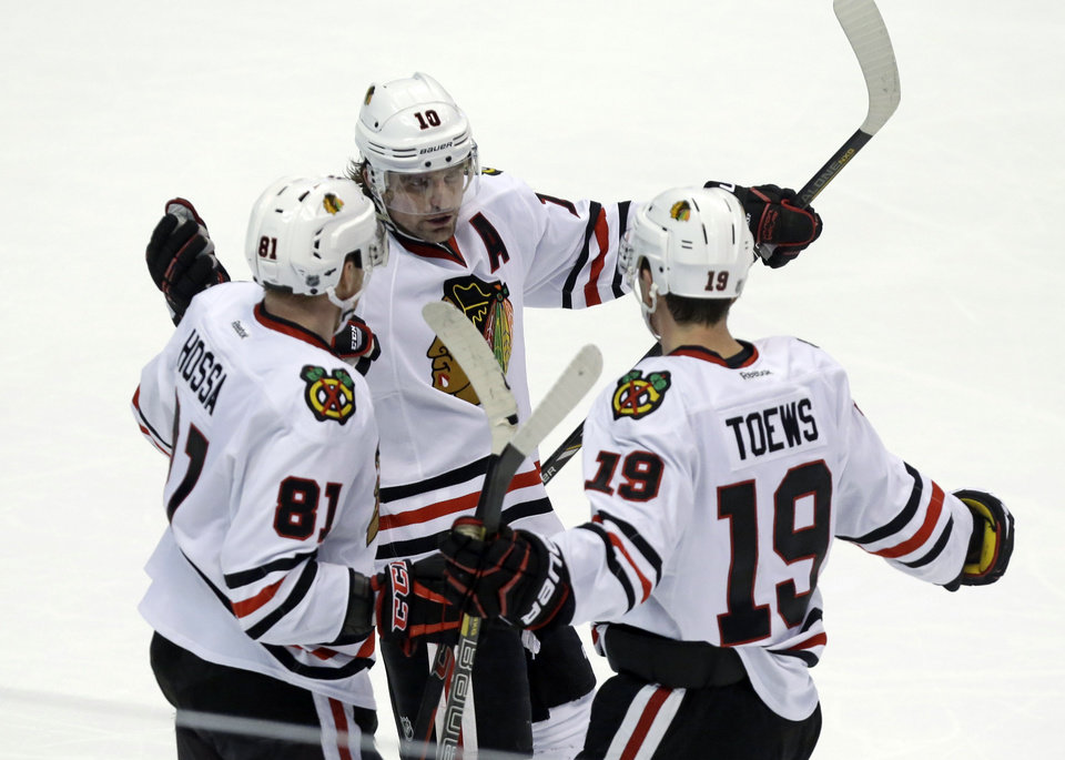Photo - Chicago Blackhawks left winger Patrick Sharp (10) and right winger Marian Hossa (81), of the Czech Republic, celebrate a goal by center Jonathan Toews (19) against the Anaheim Ducks in the third period of an NHL hockey game in Anaheim, Calif., Wednesday, Feb. 5, 2014. The Blackhawks won, 2-0. (AP Photo/Reed Saxon)