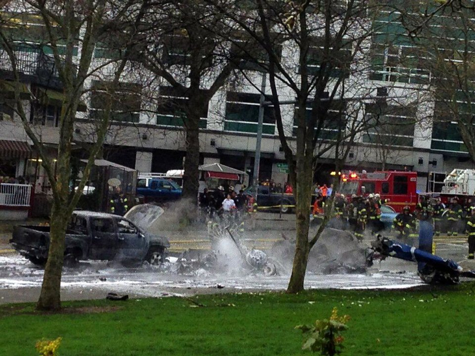 Photo - Emergency personnel respond to the scene of a helicopter crash outside the KOMO-TV studios near the space needle in Seattle on Tuesday, March 18, 2014. The station says the helicopter was apparently coming in for a landing on its rooftop Tuesday morning when it possibly hit the side of the building and went down, hitting several vehicles on Broad Street. Two people inside the helicopter were killed (AP Photo/The Seattle Times, Mike Siegel)  SEATTLE OUT; USA TODAY OUT; MAGS OUT; TELEVISION OUT; NO SALES; MANDATORY CREDIT TO BOTH THE SEATTLE TIMES AND THE PHOTOGRAPHER