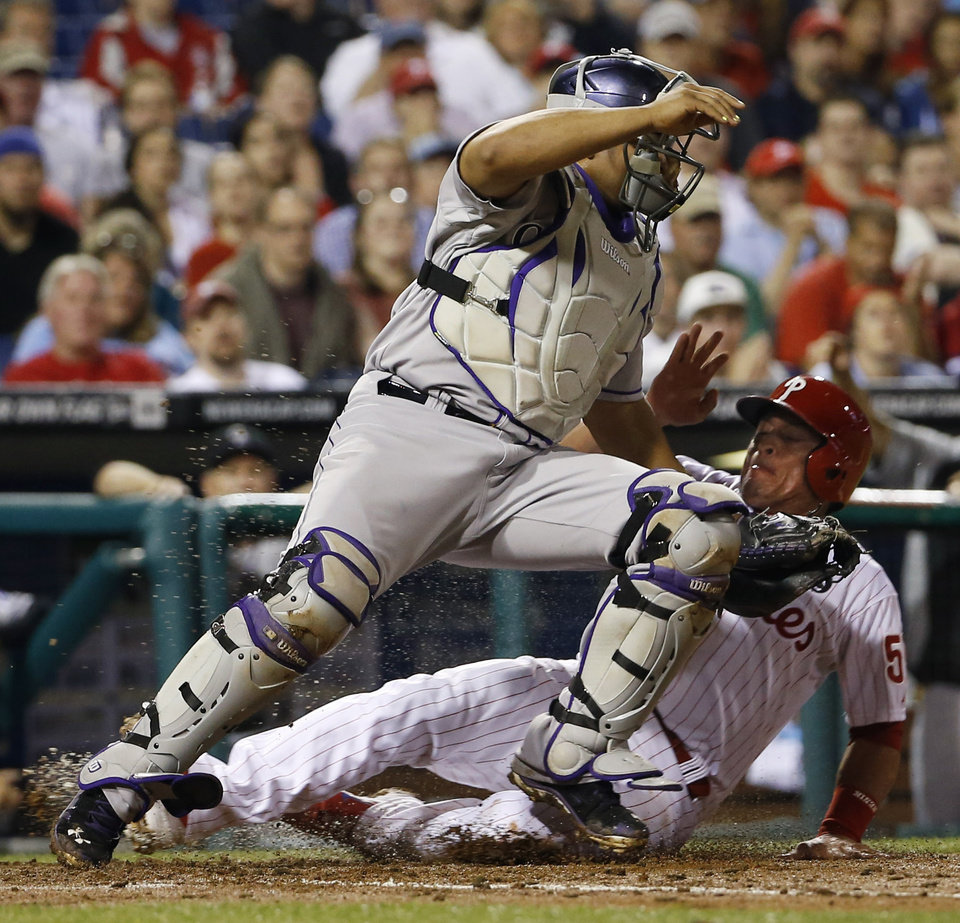 Photo - Philadelphia Phillies' Carlos Ruiz, right, collides with Colorado Rockies catcher Wilin Rosario after being forced out at home on a ball hit by Ben Revere during the third inning of a baseball game, Tuesday, May 27, 2014, in Philadelphia. (AP Photo/Matt Slocum)