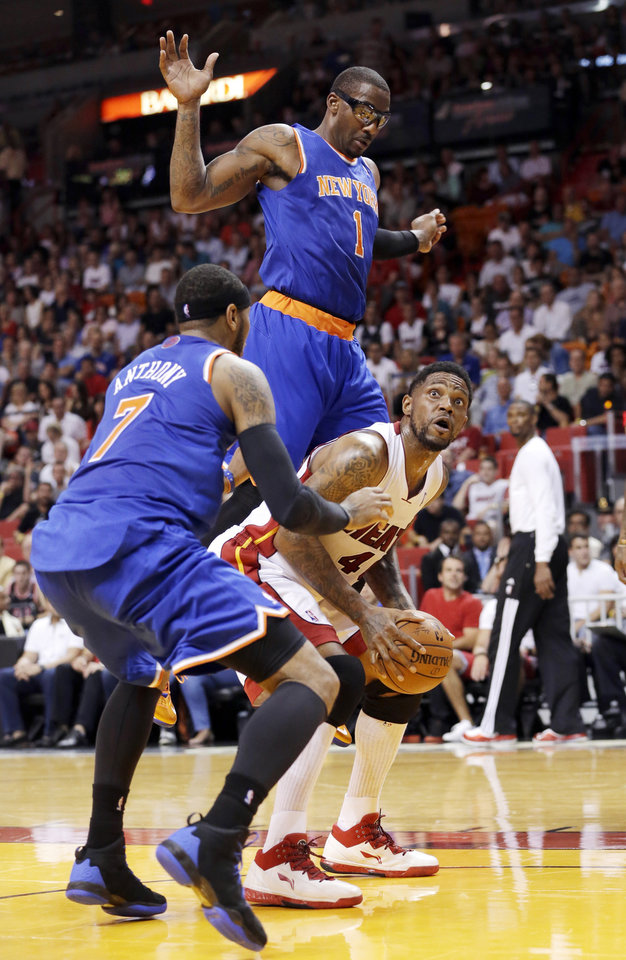 Photo - Miami Heat forward Udonis Haslem goes up for a shot against New York Knicks forward Carmelo Anthony (7) and forward Amar'e Stoudemire (1) during the first half of an NBA basketball game, Sunday, April 6, 2014, in Miami. (AP Photo/Wilfredo Lee)