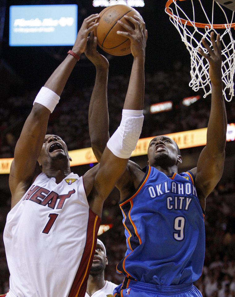 Photo - Oklahoma City's Serge Ibaka (9) goes for the ball beside Miami's Chris Bosh (1) during Game 3 of the NBA Finals between the Oklahoma City Thunder and the Miami Heat at American Airlines Arena, Sunday, June 17, 2012. Photo by Bryan Terry, The Oklahoman