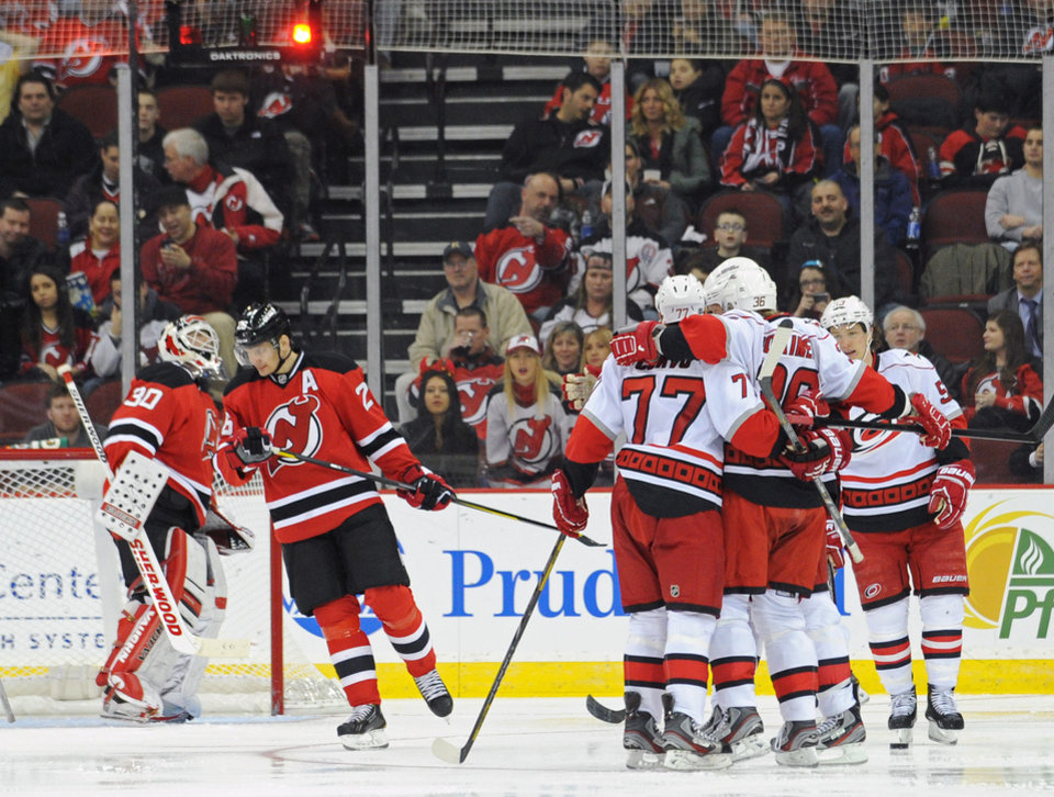 New Jersey Devils goaltender Martin Brodeur, left, and Patrik Elias, of the Czech Republic, react as the Carolina Hurricanes celebrate a goal by Jussi Jokinen during the second period of an NHL hockey game Tuesday, Feb. 12, 2013, in Newark, N.J. (AP Photo/Bill Kostroun)