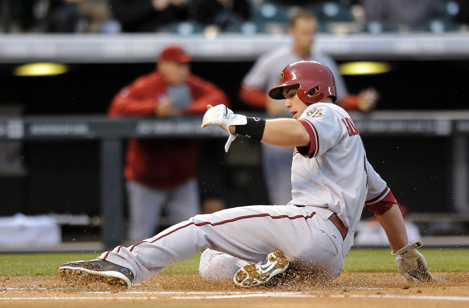 Photo - Arizona Diamondbacks Paul Goldschmidt slides safely into home base on a hit by Martin Prado in the first inning of a baseball game against the Colorado Rockies on Saturday, April 5, 2014, in Denver. (AP Photo/Chris Schneider)
