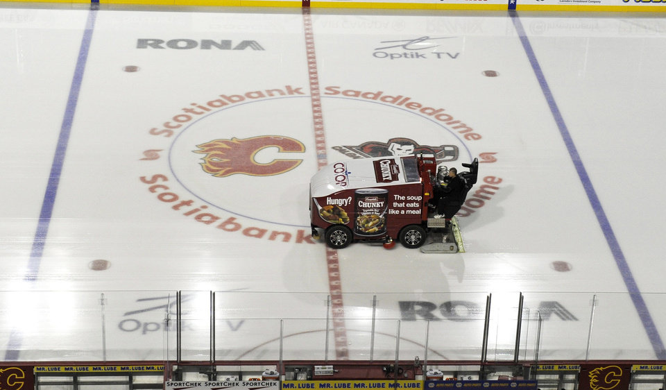 Photo - The ice surface is cleaned at an empty Scotiabank Saddledome, home of the NHL's Calgary Flames, on Sunday, Jan. 6, 2013, in Calgary, Alberta. A tentative deal to end the 113-day NHL lockout was reached early Sunday  following a marathon 16-hour negotiating session. (AP Photo/The Canadian Press, Larry MacDougal)