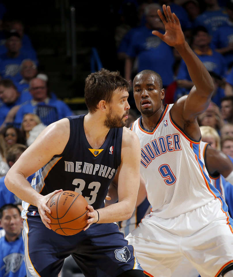 Photo - Oklahoma City's Serge Ibaka (9) defends Memphis' Marc Gasol (33) during Game 1 in the first round of the NBA playoffs between the Oklahoma City Thunder and the Memphis Grizzlies at Chesapeake Energy Arena in Oklahoma City, Saturday, April 19, 2014. Photo by Sarah Phipps, The Oklahoman