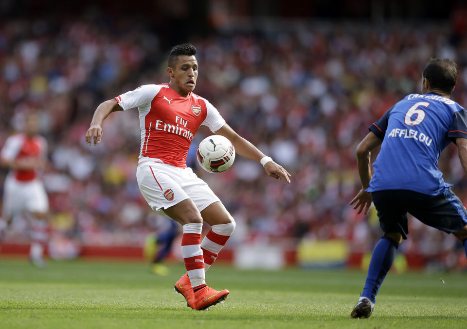 Photo - Arsenal's Alexis Sanchez, left, in action with AS Monaco's Ricardo Carvalho during the Emirates Cup soccer match between Arsenal and AS Monaco at Arsenal's Emirates Stadium in London, Sunday, Aug. 3, 2014. (AP Photo/Matt Dunham)
