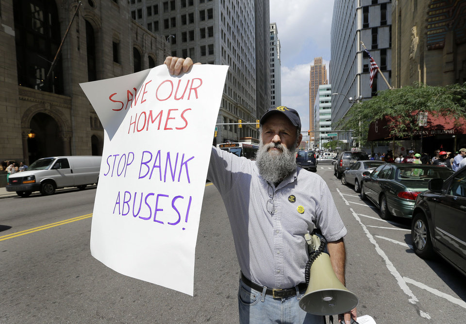 Photo - Protester John Zettner holds a sign during a rally in Detroit Monday, Aug. 19, 2013. Deadline day arrived Monday for creditors to oppose Detroit's request for bankruptcy protection, the largest municipal filing in U.S. history and one aimed at digging the beleaguered city out of billions of dollars in debt. Judge Steven Rhodes set Monday as the eligibility objection deadline in the bankruptcy petition by Detroit emergency manager Kevyn Orr. Creditors, including bond holders, insurers, banks, employee pension funds, individuals and companies that provided services, have until just before midnight to file objections electronically. (AP Photo/Paul Sancya)