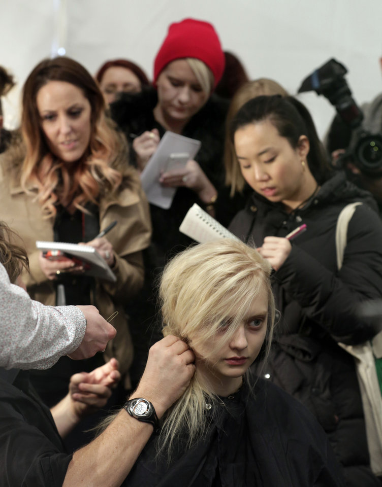 Photo - Fashion journalists take notes backstage as a model's hair is styled before the Tadashi Shoji Fall 2013 collection is modeled during Fashion Week in New York,  Thursday, Feb. 7, 2013. (AP Photo/Richard Drew)