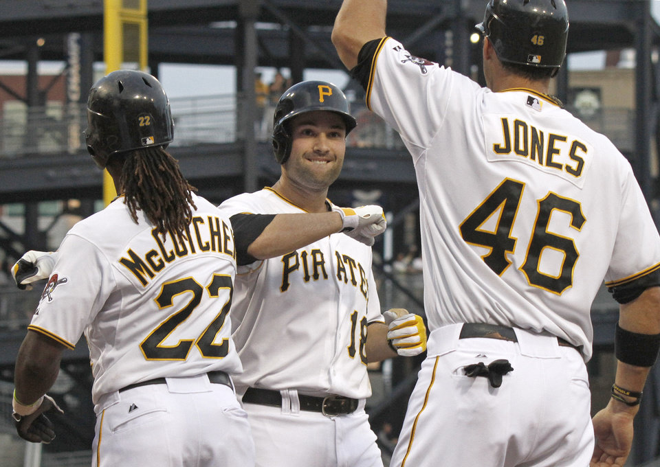 Photo -   Pittsburgh Pirates' Neil Walker (18) is greeted by Garrett Jones (46) and Andrew McCutchen (22) after driving them in with a three-run home run in the first inning of a baseball game against the Arizona Diamondbacks on Wednesday, Aug. 8, 2012, in Pittsburgh. (AP Photo/Keith Srakocic)