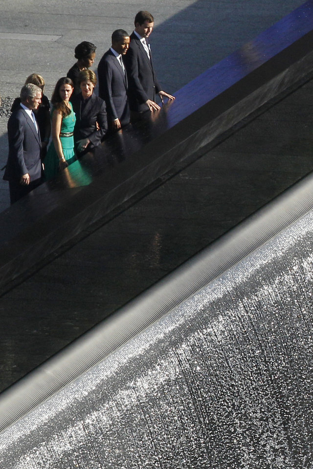 Photo -   Former President George W. Bush, left, and former first lady Laura Bush, along with President Barack Obama, second from right, and first lady Michelle Obama along with others, marking the 10th anniversary of the Sept. 11 attacks, pay their respects at the National September 11 Memorial at the World Trade Center site in Sunday, Sept. 11, 2011, in New York. (AP Photo/Matt Rourke)