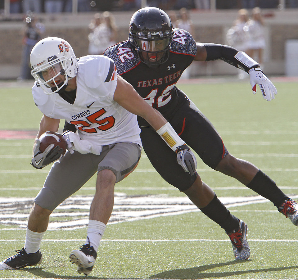 Oklahoma State Cowboys wide receiver Josh Cooper (25) runs past Texas Tech Red Raiders linebacker Daniel Cobb (42) during the college football game between the Oklahoma State University Cowboys (OSU) and Texas Tech University Red Raiders (TTU) at Jones AT&T Stadium on Saturday, Nov. 12, 2011. in Lubbock, Texas.  Photo by Chris Landsberger, The Oklahoman  ORG XMIT: KOD